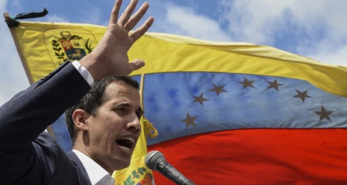 """Venezuela's National Assembly head Juan Guaido speaks to the crowd during a mass opposition rally against leader Nicolas Maduro in which he declared himself the country's """"acting president"""", on the anniversary of a 1958 uprising that overthrew military dictatorship, in Caracas on January 23, 2019. - """"I swear to formally assume the national executive powers as acting president of Venezuela to end the usurpation, (install) a transitional government and hold free elections,"""" said Guaido as thousands of supporters cheered. Moments earlier, the loyalist-dominated Supreme Court ordered a criminal investigation of the opposition-controlled legislature. (Photo by Federico PARRA / AFP)"""