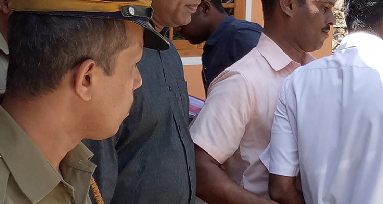 (FILES) In this file photo taken on February 28, 2017 Indian police officials escort priest Robin Vadakkumchery (C) after his arrest in Peravoor, some 300km north of Kochin in the southern Indian state of Kerala. - An Indian court has convicted a senior Catholic priest of raping a minor and sentenced him to 20 years in jail, the latest sexual assault scandal involving the Church in southern Kerala state. Robin Vadakkumchery was found guilty on February 16, 2019 of raping a 16-year-old schoolgirl who became pregnant, with the crime only coming to light after the victim gave birth to a baby in a surprise delivery in February 2017. (Photo by STR / AFP)
