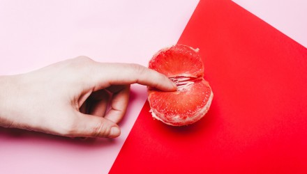 Concept sex, masturbation. Hand, fingers in grapefruit, vagina symbol on a red background