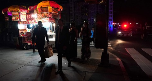 TOPSHOT - People walk down the streets during a major power outage affecting parts of New York City on July 13, 2019. Subway stations plunged into darkness and the billboards of Times Square suddenly flicked off as New York's Manhattan was hit by a power outage on Saturday. About 42,000 customers lost electricity in the early evening, according to the Con Edison utility, which did not give a reason for the cut.  / AFP / TIMOTHY A. CLARY