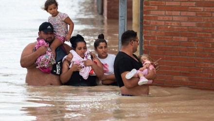 Peolple carry children on a flooded street in Almoradi on September 13, 2019. - Two more people died as torrential rain and flash floods battered southeastern Spain, raising the death toll to four as the storm caused havoc for travellers and forced 3,500 people from their homes. (Photo by JOSE JORDAN / AFP)